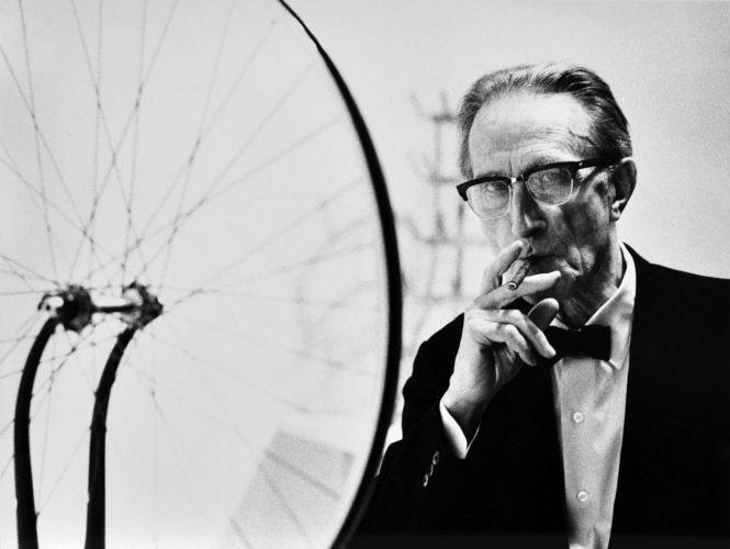 Julian Wasser Duchamp smoking Cigar next to Bicycle Wheel, Duchamp Retrospective, Pasadena Art Museum, 1963 Vintage gelatin silver print - 7.5 x 10 inches - courtesy robert Berman Gallery