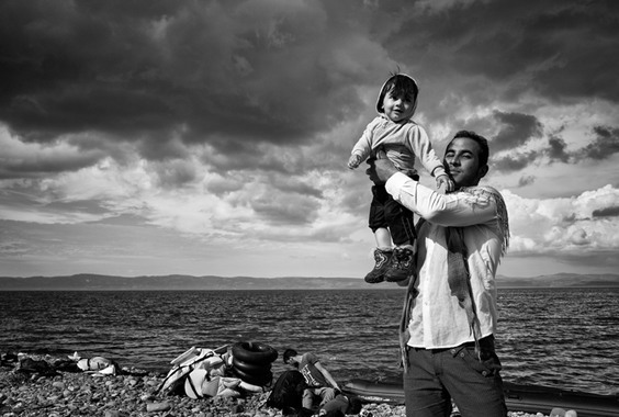 Lesbos, Greece, October 2015: A father celebrates with his child on the Greek island of Lesbos after a stormy crossing with his family over the Aegean Sea from Turkey. Photo by: Tom Stoddart